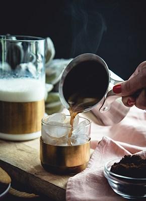 Dampfender Kaffee im Glas mit Milch