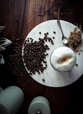 Holztisch mit Kaffee und aufgeschäumter Milch