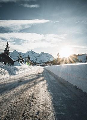 verschneite Straße im Winter mit Sonnenuntergang
